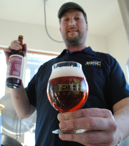 "Kevin Crompton holding his newest creation ""Brainless on Raspberries"" This is a belgiun-style ale infused with raspberries, Mikey's Beer Blog describes it as ""A nose of earthy raspberries... the spices and esters of the base Belgian ale. Next comes the dry, subdued raspberry notes that have an almost vinous quality."" Epic's store is located at 825 S State St."