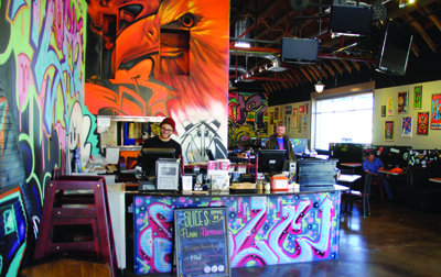 Above, Este Pizza employees show off the meats and veggies of their efforts. Below, the new seating area shows off graffiti murals, and  offers three times the seating that their old location did.