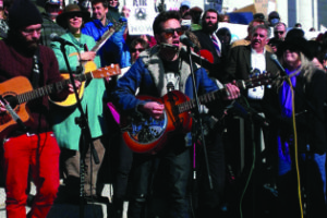 Tom Bennett (center) performing before a crowd of 5,000 at the Clean Air, No Excuses Rally at the Capitol in January.