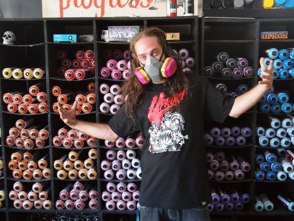 Owner Chase Jensen demonstrates the variety of graffiti paints his store sells.
